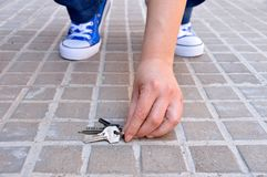 Finding the keys. Cropped shot of a young finding the keys in the street sidewalk royalty free stock photos