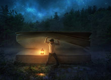 Finding a large Bible at night. A man lifts the pages of a large Bible at night Stock Photo