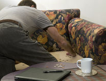 Finding loose change on couch Stock Image
