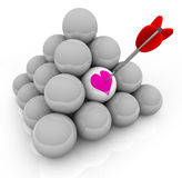 Finding Love in the Hunt for Romance and Passion. A pyramid of white balls with an arrow stuck in one that shows a pink heart, symbolizing the hunt for love and Royalty Free Stock Photography