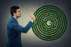 Finding maze solution. Young businessman holding a pencil in his hand try to find the solution of a imaginative round maze, drawing a red line to success. Circle Stock Photos