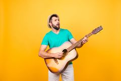 He is finding notes for the new popular song! Cheerful joyful ex. Cited musician playing the acoustic guitar, isolated on yellow background Royalty Free Stock Image