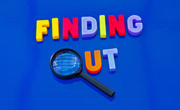 Finding out. Text 'finding out' in colorful uppercase letters with letter 'o' replaced by the lens of a hand magnifier, blue background Stock Images
