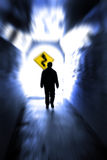 Finding a Path Through Sorrow. Person in long tunnel walkway with white light at the end and a sign showing curves ahead stock photography