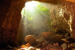 Finding that perfect light. Gorgeous light rays shining down into a sacred limestone cave royalty free stock photography