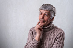 Finding perfect solution. Mature handsome man with gray hair and wrinkles holding his finger on cheek looking thoughtful and havin Stock Images