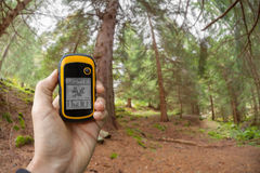 Finding the right position in the forest via gps ( blurred background) Stock Photos
