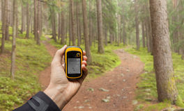 Finding the right position in the forest via gps ( blurred background) Royalty Free Stock Image
