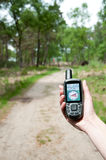 Finding a route. A woman hand hold a GPS device to secure the route through the forest Royalty Free Stock Photography