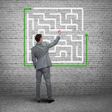 Finding solution. Back view of businessman drawing labyrinth on wall Stock Image