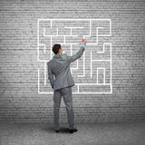 Finding solution. Back view of businessman drawing labyrinth on wall Stock Photo