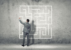 Finding solution. Back view of businessman drawing labyrinth on wall Royalty Free Stock Image