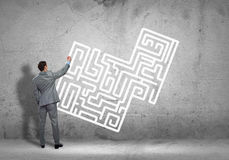 Finding solution. Back view of businessman drawing labyrinth on wall Stock Photography