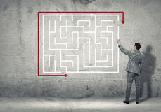 Finding solution. Back view of businessman drawing labyrinth on wall Stock Images