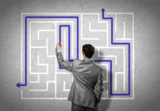 Finding solution. Back view of businessman drawing labyrinth on wall Stock Photos