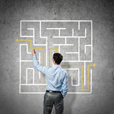 Finding solution. Back view of businessman drawing labyrinth on wall Royalty Free Stock Photo