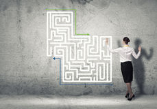 Finding solution. Back view of businesswoman drawing labyrinth on wall Stock Images