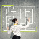 Finding solution. Back view of businesswoman drawing labyrinth on wall Royalty Free Stock Photos