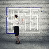 Finding solution. Back view of businesswoman drawing labyrinth on wall Stock Photo