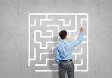 Finding solution. Business man draws a maze on the wall, the concept of finding a solution in business Stock Photos