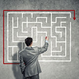 Finding solution. Business man draws a maze on the wall, the concept of finding a solution in business Royalty Free Stock Image
