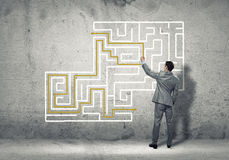 Finding solution. Business man draws a maze on the wall, the concept of finding a solution in business Royalty Free Stock Photos
