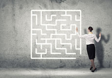 Finding solution. Business woman draws a maze on the wall, the concept of finding a solution in business Royalty Free Stock Images