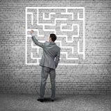 Finding solution. Businessman drawing a maze on the wall Stock Photos