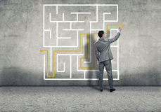 Finding solution. Businessman man draws a maze on a concrete wall Royalty Free Stock Image