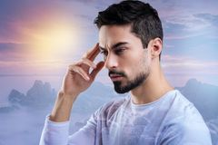 Smart young engineer thinking about an urgent problem and touching his forehead stock photography
