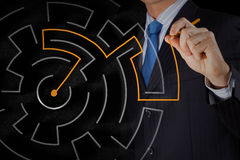 Finding solution. Close up of businessman drawing way out of labyrinth Stock Images