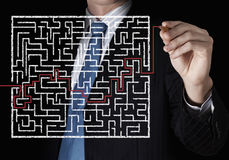 Finding solution. Close up of businessman drawing way out of labyrinth Royalty Free Stock Photos