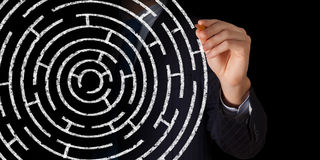 Finding solution. Close up of businessman drawing way out of labyrinth Royalty Free Stock Photography