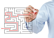Finding the solution concept. Human hand drawing red arrow through the labyrinth Stock Image