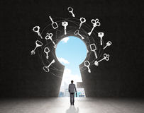 Finding a solution. A man with a case standing in front of a huge keyhole, many keys drawn around it, city and sky seen through it. Black background. Back view Royalty Free Stock Images