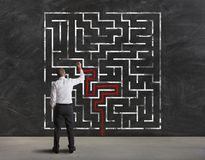Finding the solution of maze. Businessman finding the solution of a maze Stock Image