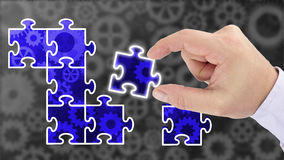 Finding a solution putting together the pieces. Hand putting pieces of a puzzle together revealing a blue glowing cogs finding a solution business success Royalty Free Stock Photography
