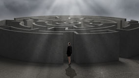 Finding solution. Thoughtful businesswoman standing near the enter of labyrinth Stock Image