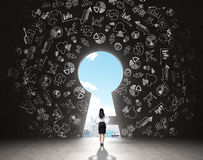 Finding a solution. A woman with hands on hips standing in front of a huge keyhole, many business icons drawn around it, city and sky seen through it. Black Stock Photography