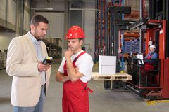 Finding solution - Workers & boss in warehouse. Boss talking to worker in uniform in factory stock photography
