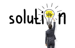 Finding a solution. Young businessman painting a bright yellow bulb with a brush in the word 'solution' instead of the second 'o' on the white wall. Back view Royalty Free Stock Photos