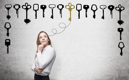 Finding a solution. Young woman with hand to the chin looking up in search of the right solution which are presented as keys around her. Concrete background Royalty Free Stock Photography