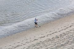 Finding Treasure at the Beach. A lone metal detectorist on the hunt for buried treasures stock photos