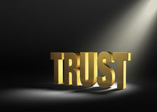 Finding Trust. Angled spotlight revealing shiny gold TRUST on a dark background Stock Photography