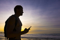 Finding the way. Silhouette of muscular male hiker exploring beach at sunset while holding celular smart phone as he gazes far ahead Stock Photos