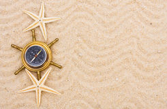 Finding your travel destination. A compass sitting on a sand background, Finding your travel destination Royalty Free Stock Photo