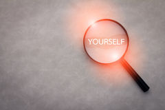Finding yourself concept with word and magnify.jpg. Finding yourself concept with word and magnify on grey leather background.jpg Royalty Free Stock Photo