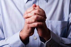 Fine alta o primo piano delle mani di pregare maturo fedele dell'uomo Immagine Stock