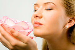 Fine aroma. Portrait of beautiful woman holding a flower and smelling it Stock Images