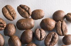 Fine arrostita di macro dei chicchi di caffè sul modello di struttura su fondo bianco Fotografia Stock Libera da Diritti